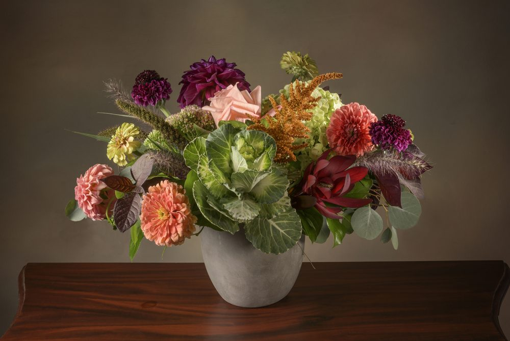 Fresh flowers in an autumn arrangement of warm coral, deep pink and purple colors delivered