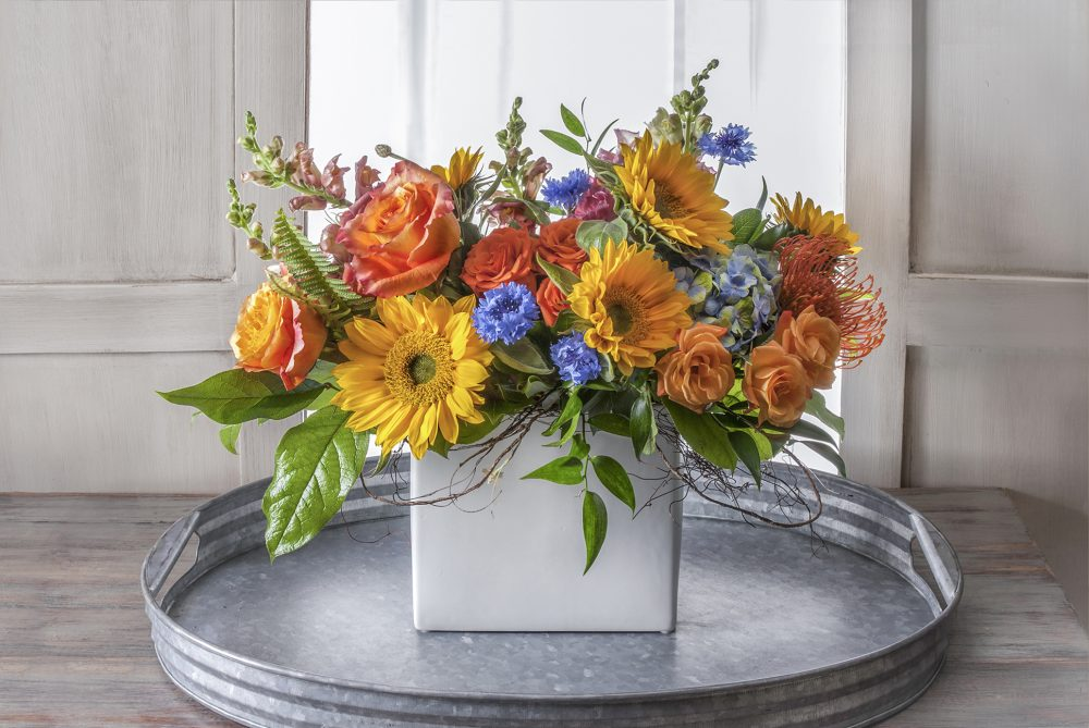 Fresh flowers in bright autumn colors of sunflower yellow, orange, and a touch of sky blue.