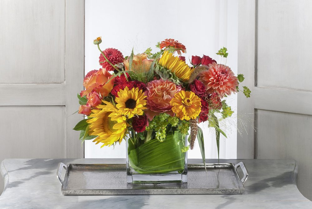 Unique gift fresh flower arrangement in bright autumn colors of sunflower yellow, coral, and orange.