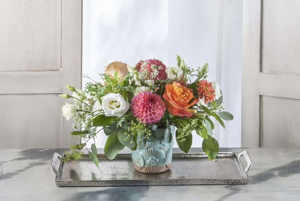 A unique gift of fresh flower arrangement with cheerful colors of coral, white, peach, and orange.