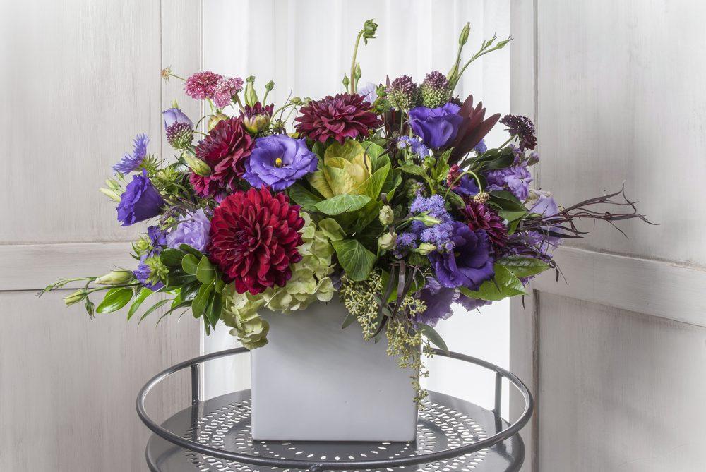 Unique gift fresh flower arrangement in autumn jewel tones in deep purple and garnet reds designed with autumn flowers.