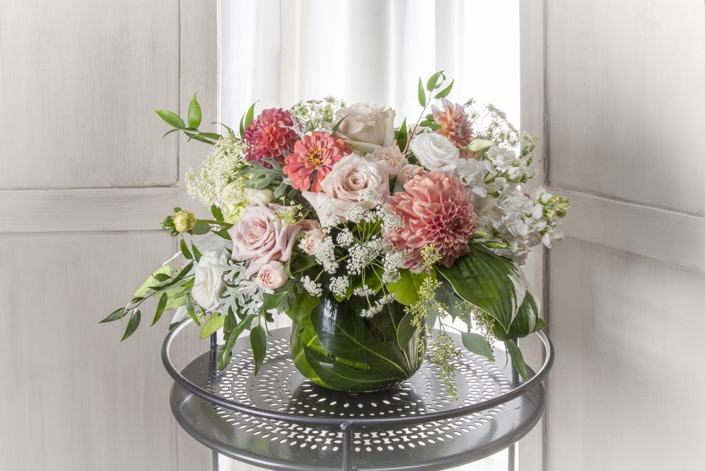 Unique gift fresh flower arrangement in bright autumn flowers in colors of coral, peach, and white.
