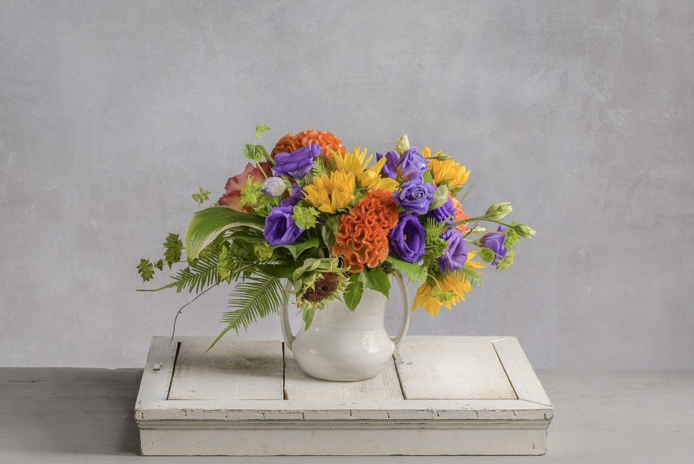 Bold and bright autumn colors in sunflower yellow, orange, and purple in our fresh flower arrangement.