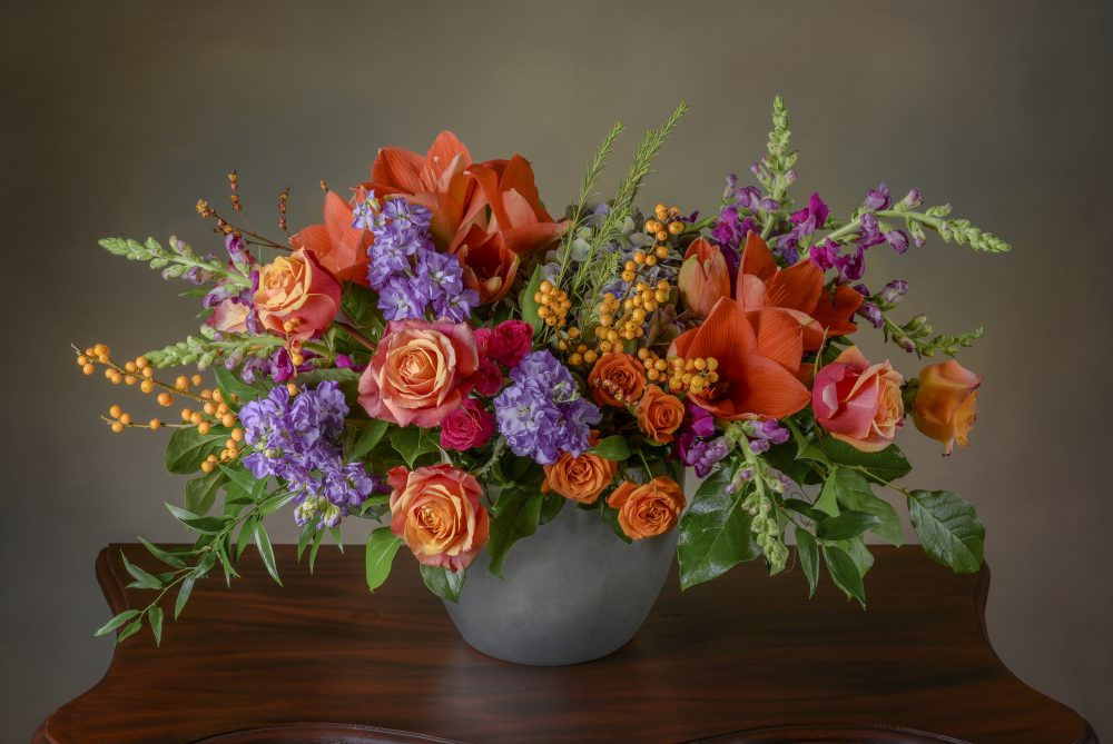 Fresh flowers in a bright autumn arrangement of warm orange, apricot, and violet colors delivered