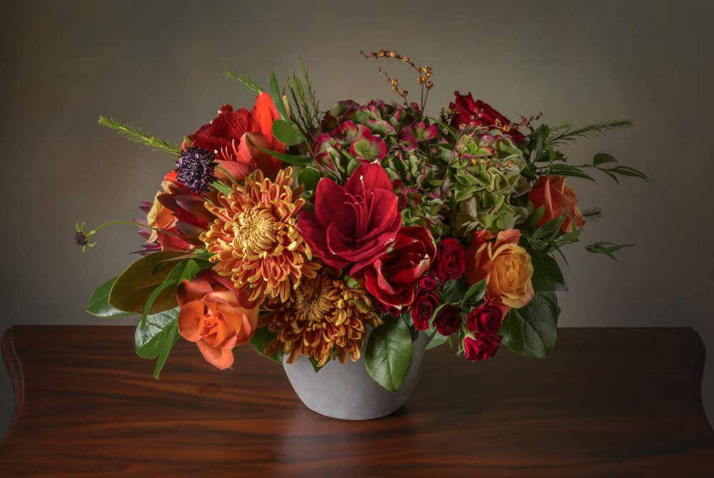 Fresh flowers in a vibrant autumn arrangement of russet, orange, and red colors delivered