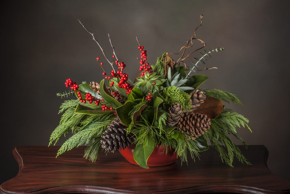 Lush winter holiday arrangement in evergreens and bright red berries with cones and pods delivered.