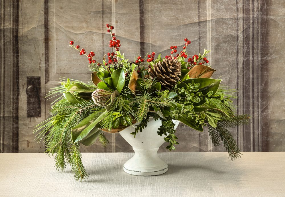A RWF Original fresh evergreen, succulent and berries arranged with magnolia in a pedestal urn.