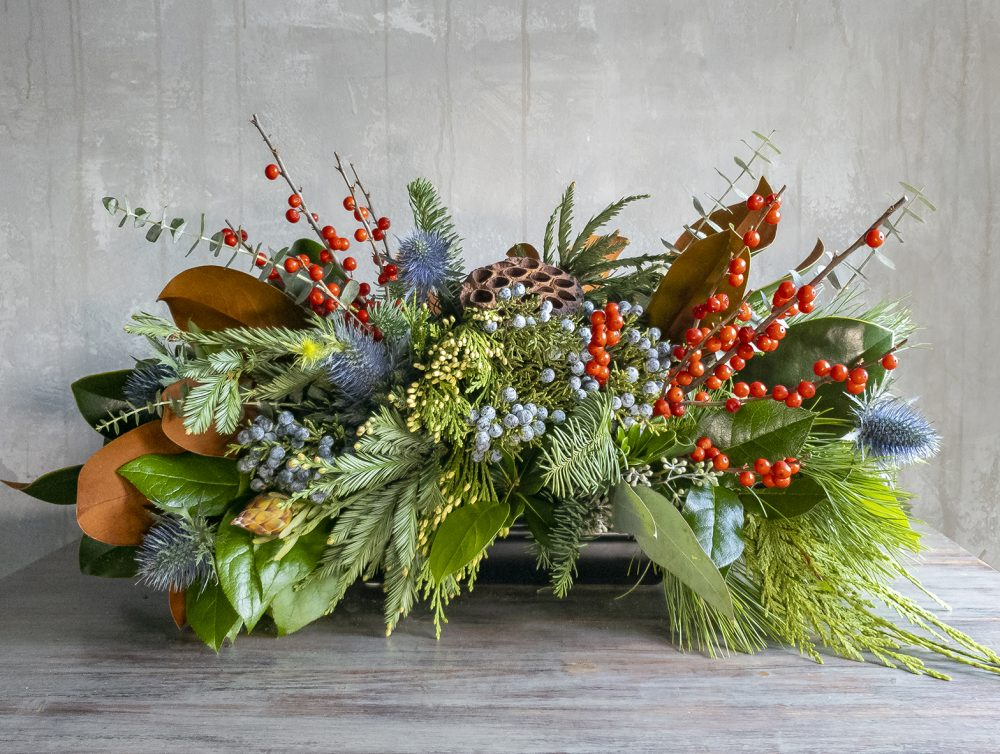 Holiday flower class unique arrangement in long and low style with evergreens, berries, and botanical accents.