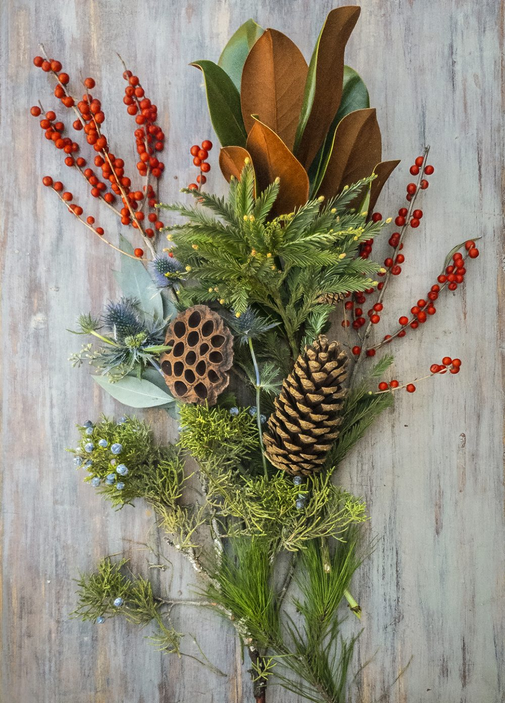 Holiday flower arranging class in long and low style with evergreens, berries, and botanical accents.