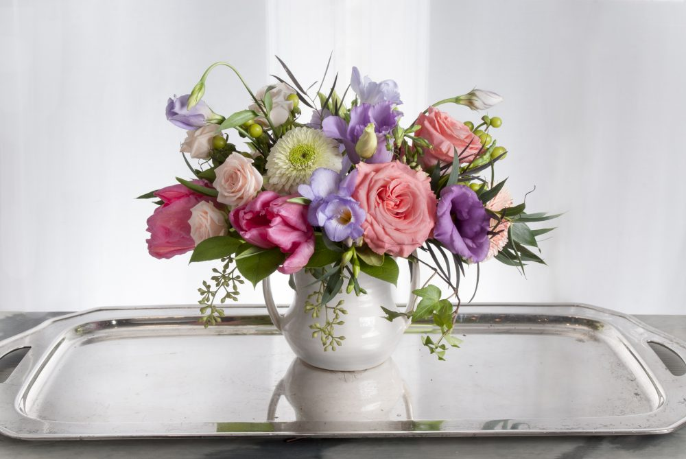 Colorful spring fresh flower arrangement in two handled pot delivered.