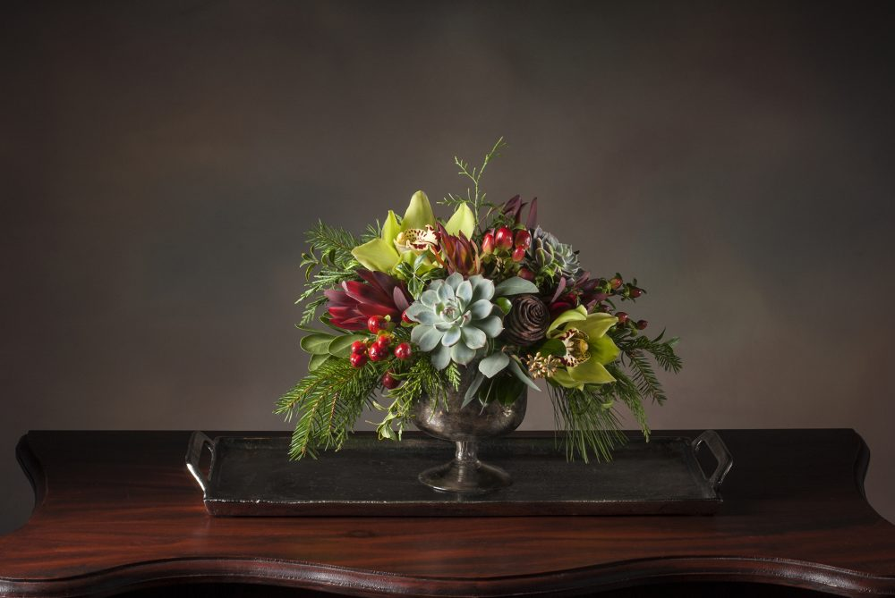 Lovely and unique fresh flower arrangement in bright greens, rich reds, accented with evergreens and silvery succulents delivered