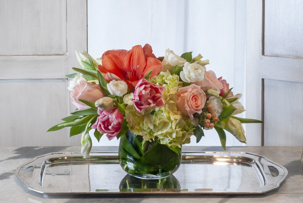 Colorful coral and pink with white unique fresh flowers in a spring arrangement gift delivered.