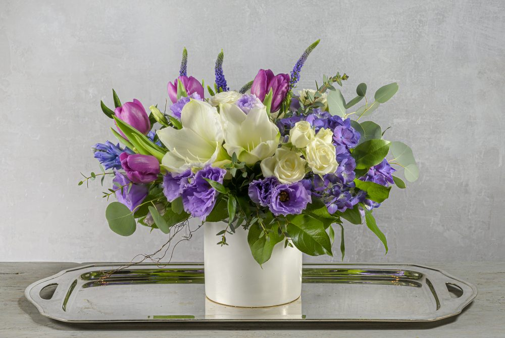 Colorful winter fresh flower arrangement in lavender, purple, and white blooms unique gift delivered.