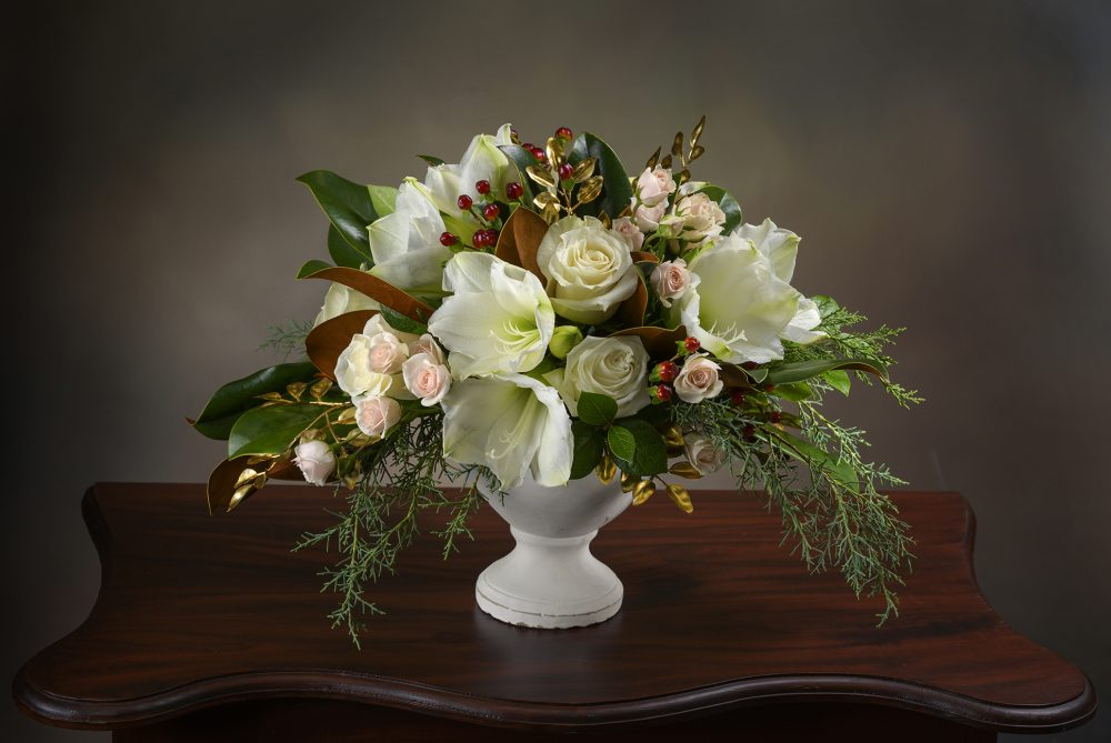 Lush winter white and peach flower arrangement with accents of gold in a white urn