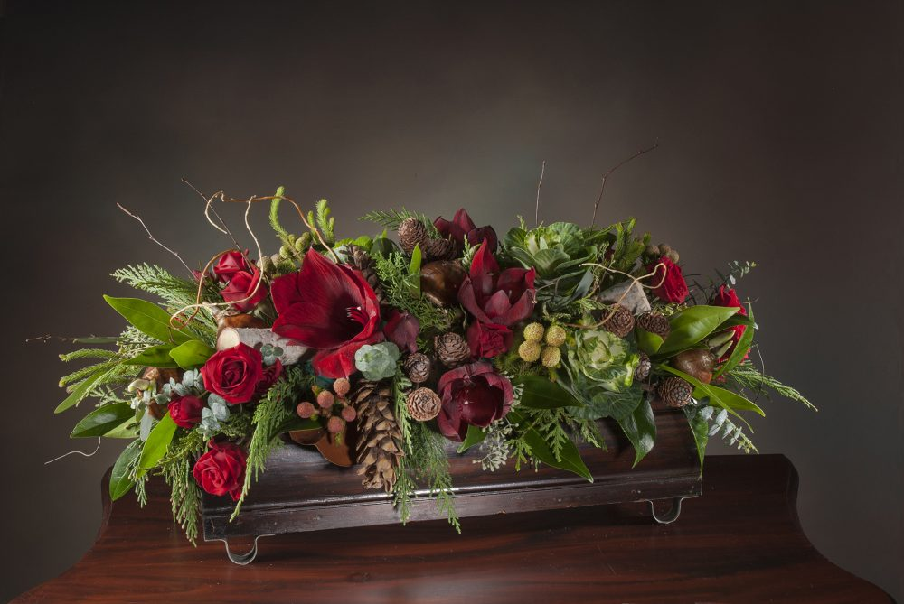 Red amaryllis flowers with accents and evergreens in a RWF Original container, holiday centerpiece delivered