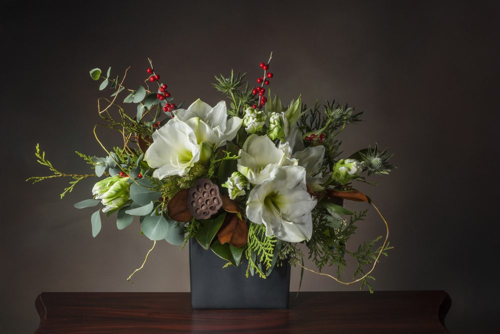 Beautiful white amaryllis flower arrangement with accents of red berries and evergreens delivered
