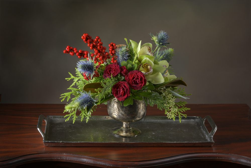Lovely unique fresh flower arrangement in rich reds, and blue thistle accented with evergreens and berries delivered
