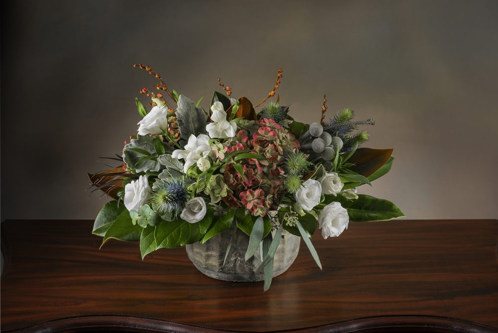 Unique fresh flower arrangement with magnolia foliage, berries and soft flowers delivered