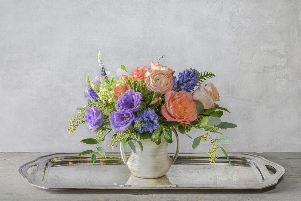 Colorful fresh flower arrangement in two handled pot delivered.