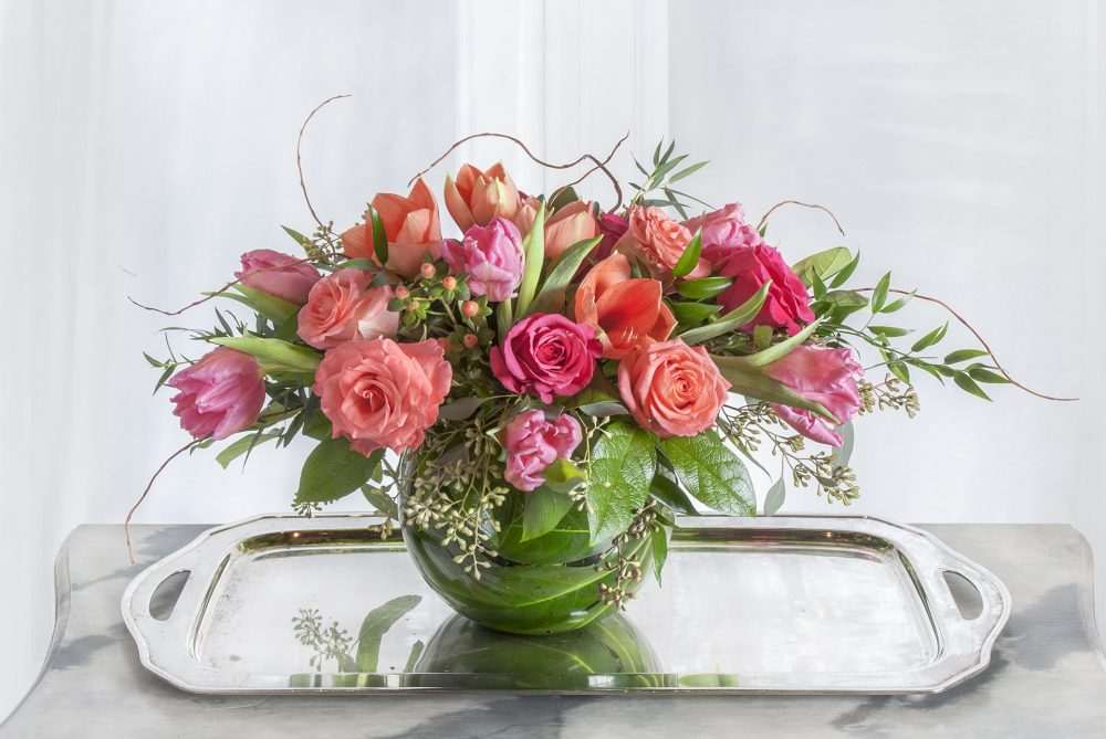 spring fresh flower arrangement with pink tulips, roses, and amaryllis in an emerald leaf vase