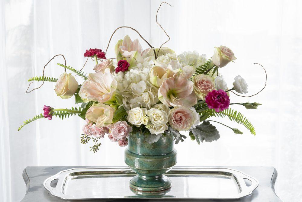 pretty pastel feminine valentine fresh flower arrangement in an aqua urn