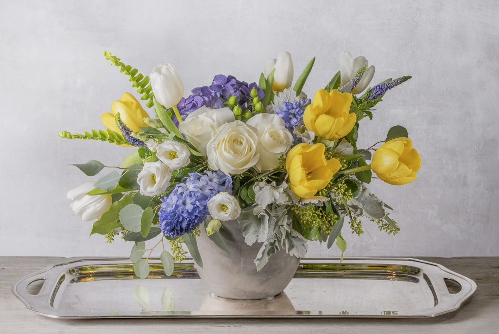 Blue, white and yellow spring flowers with Holland tulips in a unique spring arrangement delivered.