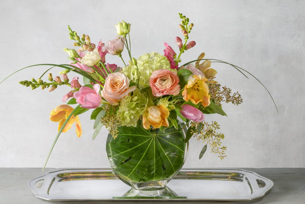 Elegant spring fresh flower arrangement in bright pink, peach, and yellow blossoms arranged in an emerald leaf wrapped slim vase delivered