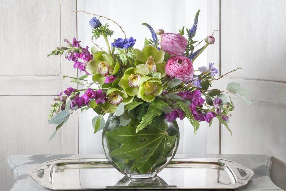 fresh flower arrangement in bright colors of pink and purpled blossoms with orchids delivered