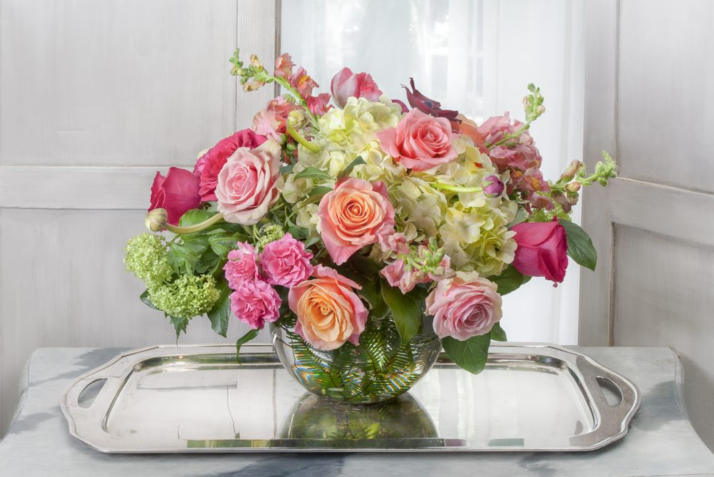 Unique gift of lush fresh flowers delivered in bright spring colors of pink, coral, and orange in a rose bowl for any occasion