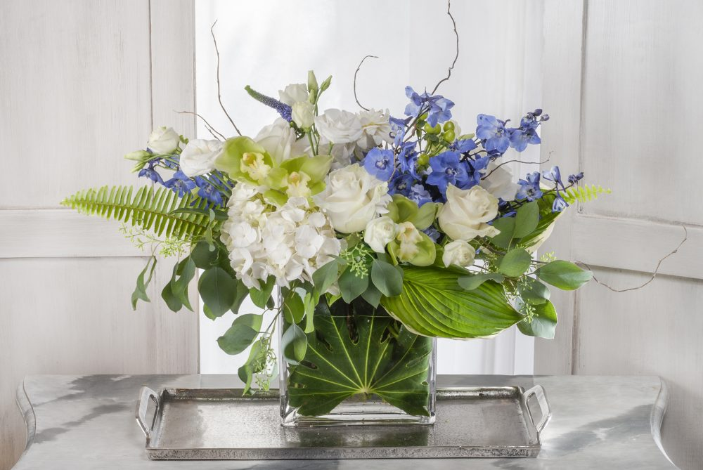 Fresh flower arrangement delivered with bright white and blue blossoms in an emerald leaf wrap