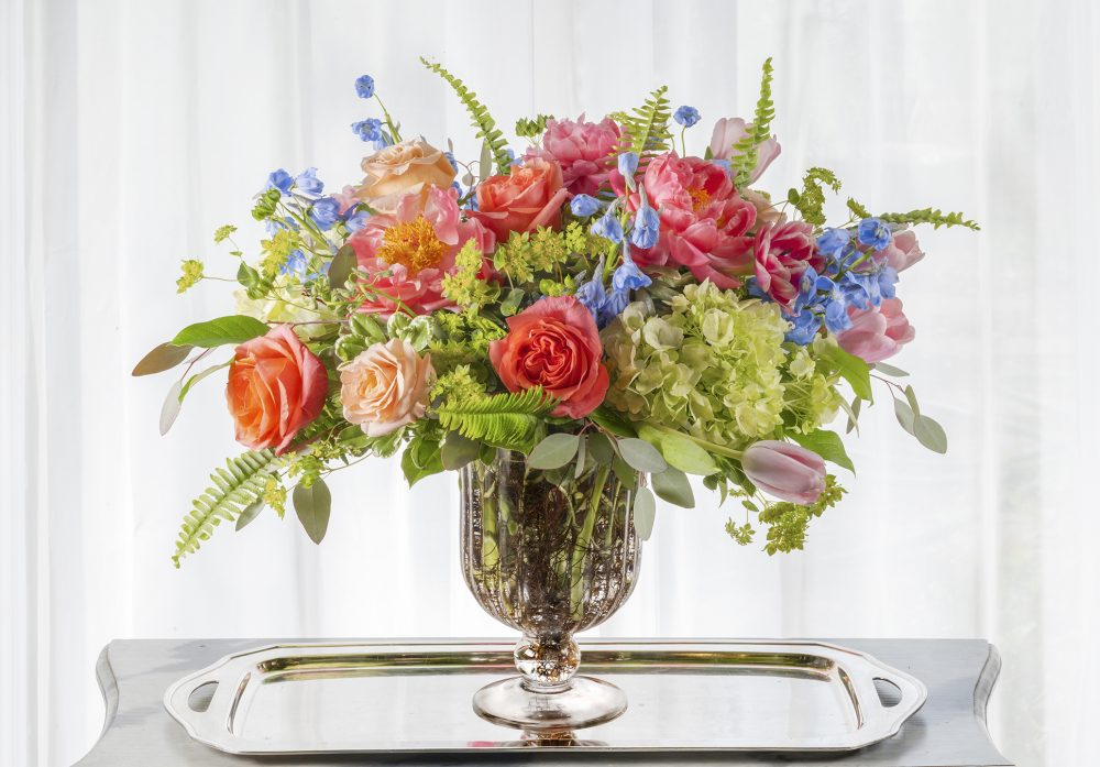 Unique delivered gift of fresh flowers with coral peonies and bright accent flowers in spring colors of coral, blue, and orange in a fluted pedestal vase
