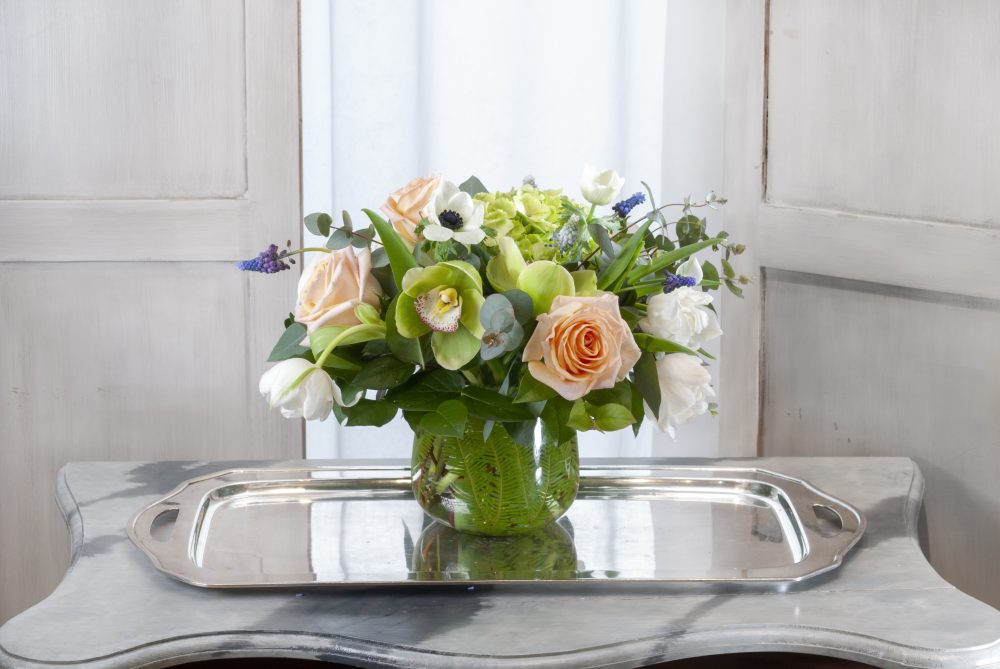 ): spring fresh flower arrangement with peach roses, tulips, and green orchids in an emerald leaf vase