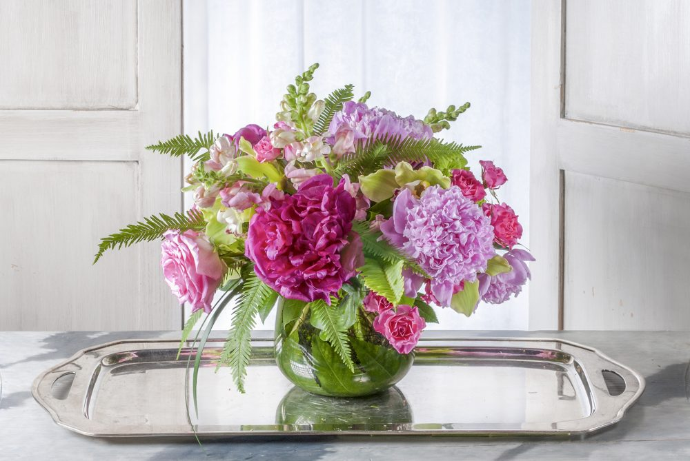 Unique gift of lush fresh flowers delivered in bright pink and magenta peonies with spring flowers in an emerald leaf wrap for delivery