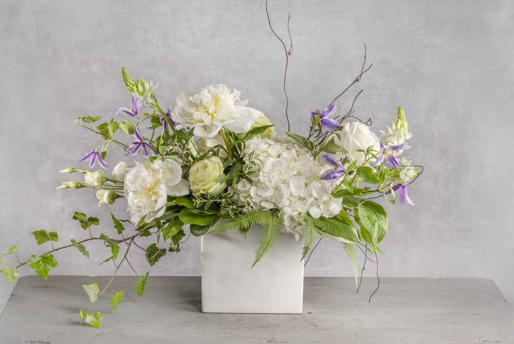 Unique gift of fresh flowers delivered in white vase with white peonies, roses, clematis flowers