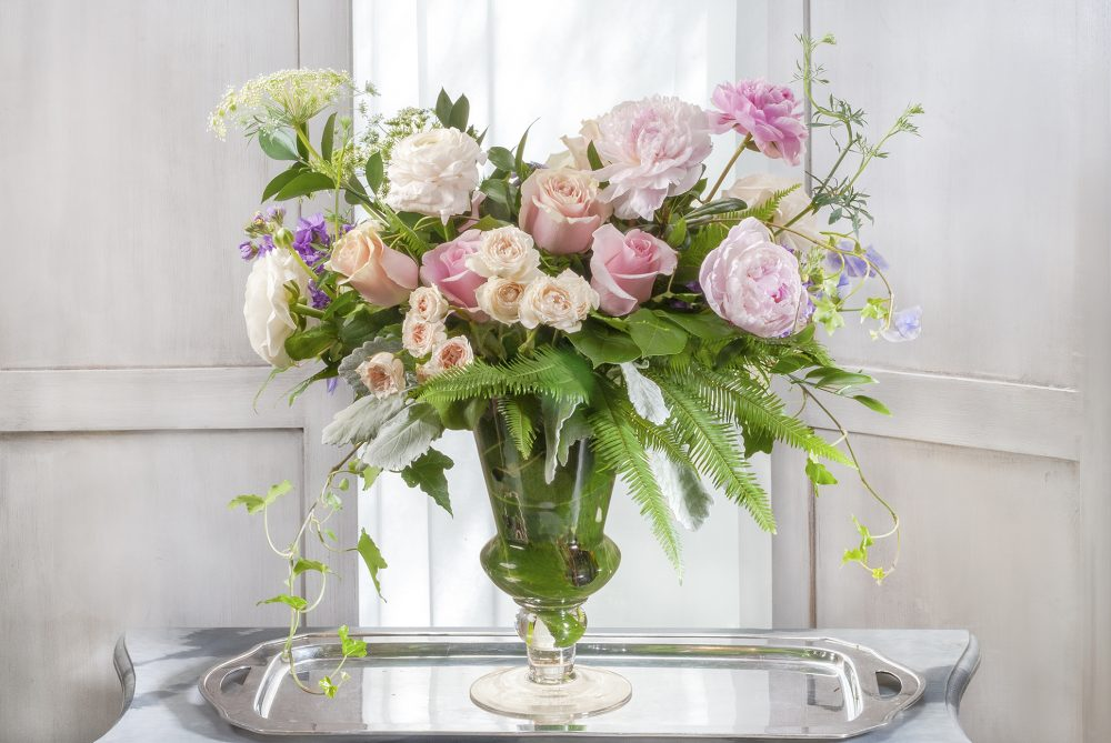 Gift of unique fresh flowers with peonies and roses in pastel colors designed in a tall pedestal vase