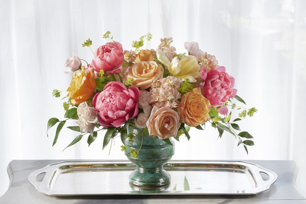 Vibrant warm colors in coral peonies, pinks, and orange melon flowers in a fresh arrangement delivered