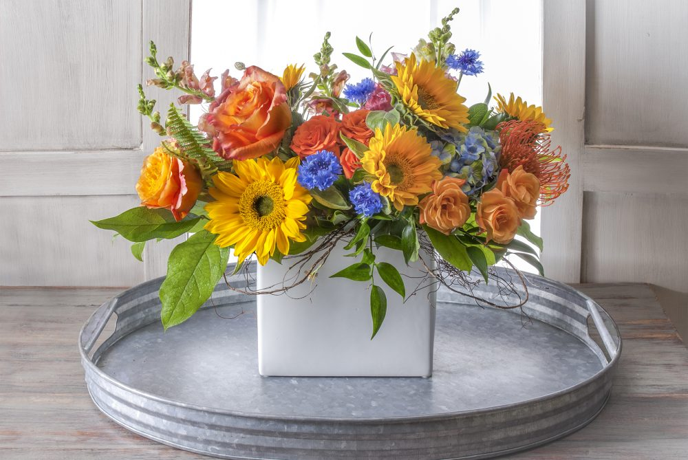 Cheerful gift of lush fresh flowers delivered in bright summer colors of golden yellow, orange, and accents of blue in a slim vase, lovely for any occasion