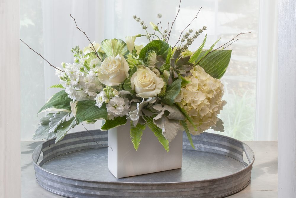 Lovely gift of fresh flowers delivered in white, green, and sage accents in a slim vase, lovely for any occasion