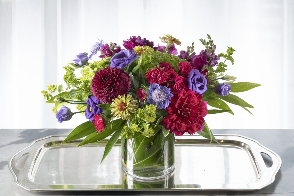 Gift of unique fresh flowers with beautiful summer field flowers and dahlias in bold purples and deep magenta colors designed in a cylinder vase