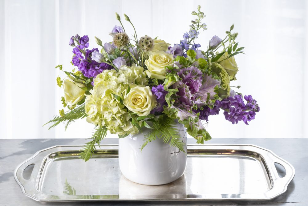 Unique gift of fresh flowers arrangement with summer field flowers in lavender, purple, and green.