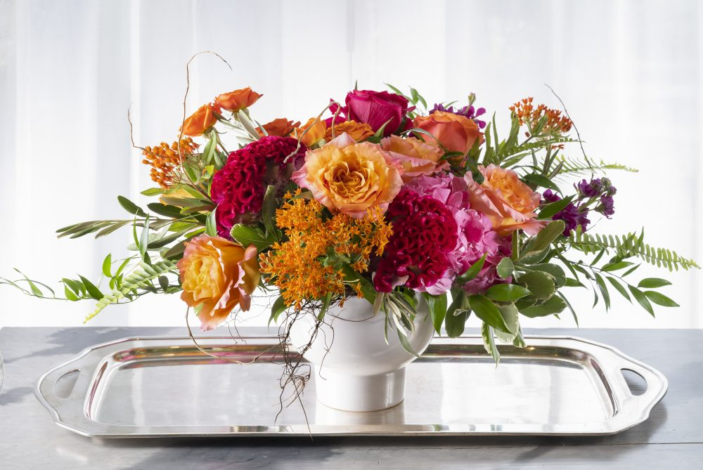 Fresh flowers arrangement gift with vibrant summer flowers in orange, magenta, and pink.
