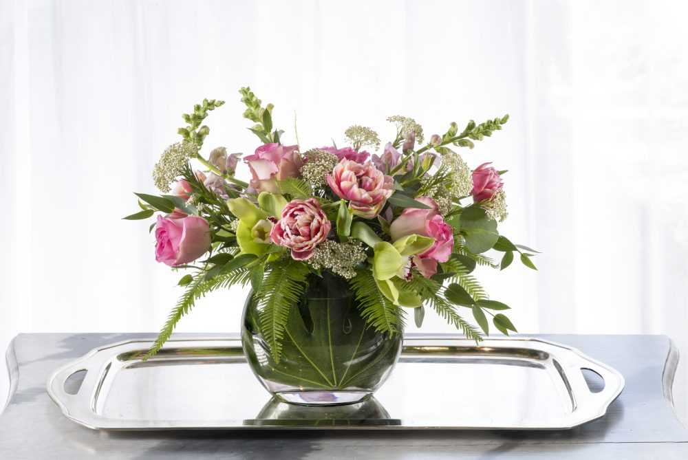 Bold arrangement of sunflowers and accent blooms in a striking black vase, delivered