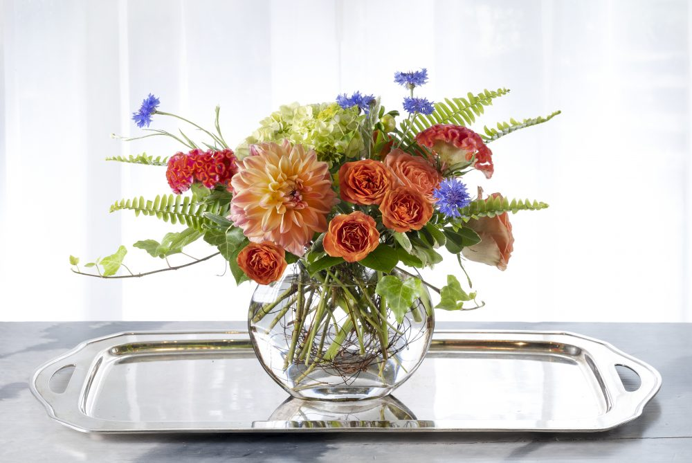 Sweet unique gift of fresh flowers arrangement with summer flowers in orange, peach, and blue, and green.