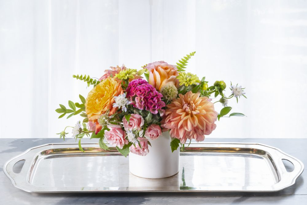 Sweet peach, pink, bright green fresh flowers with dahlias in a summer arrangement for gifting.